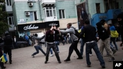 FILE - Pro-Ukrainian activists clash with pro-Russia activist during a pro Ukraine rally in Donetsk, Ukraine.
