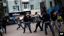 FILE - Pro-Ukrainian activists clash with pro-Russia activist during a pro Ukraine rally in Donetsk, Ukraine.