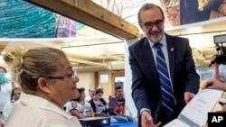 FILE - Carlos Sada, Mexico's consul in Los Angeles presents Irma Rodriguez Guevara, from El Salvador (L), with her computer studies certificate in Los Angeles, Sept. 3, 2015.