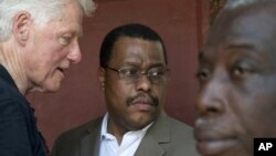 Former U.S. President and UN special envoy to Haiti, Bill Clinton, left, speaks to Garry Conille, center, on the outskirts of Port-au-Prince, Haiti. (August 2011 file photo)