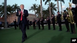 FILE - President Donald Trump listens to the Palm Beach Central High School Band as they play at his arrival at Trump International Golf Club in West Palm Beach, Florida, Feb. 5, 2017.