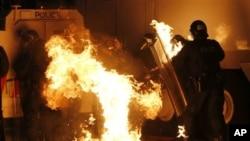 Perusuh melembarkan bom molotov ke arah polisi dalam kerusuhan di Belfast, Irlandia Utara Sabtu malam (13/7).