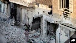ໃນພາບຖ່າຍຂອງວນທີ 28 ກໍລະກົດ, 2012 ຄອບຄົວຂອງຊາວຊີເຣຍ ຄອບຄົວນຶ່ງຢືນຢູ່ເທິງຊາກ ຫັກພັງຂອງເຮືອນຢູ່ຄຸ້ມ Maarat al--Numaanຢູ່ຂອບຊາຍແດນທາງຕາເວັນອອກຂອງແຂວງ Idlib, ທາງພາກເໜືອຂອງຊີເຣຍ.