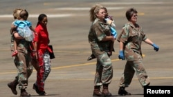 Members of the South African Army carry two children, who sustained injuries in a collapsed church guesthouse in Lagos and were evacuated from Nigeria, as they arrive at an air force base north of Johannesburg, Sept. 22 2014.