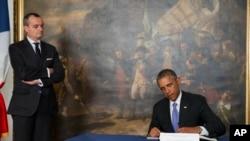 رییس جمهوری اوباما در حال امضای دفتر یادبود در سفارت فرانسه