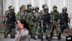 Cảnh sát bán quân sự Trung Quốc trang bị với lá chắn và dùi cui tuần tra gần Quảng trường Nhân dân ở Urumqi, ngày 23/5/2014.