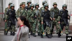 Paramilitary policemen with shields and batons patrol near the People's Square in Urumqi, China's northwestern region of Xinjiang, May 23, 2014.