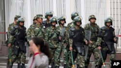 FILE - Paramilitary policemen with shields and batons patrol near the People's Square in Urumqi, China's northwestern region of Xinjiang.