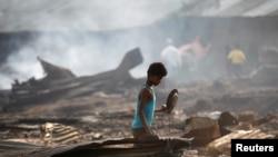 Seorang anak laki2 mencari barang-barang yang dianggap masih berguna di antara benda-benda yang hangus terbakar setelah kebakaran memporak porandakan kamp penampungan pengungsi Rohingya di dekat Siitwe, Myanmar (3/5).