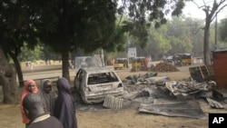 Children stand near the scene of an explosion in a mobile phone market in Potiskum, Nigeria, Jan. 12, 2015. Two female suicide bombers targeted the busy marketplace on Sunday.