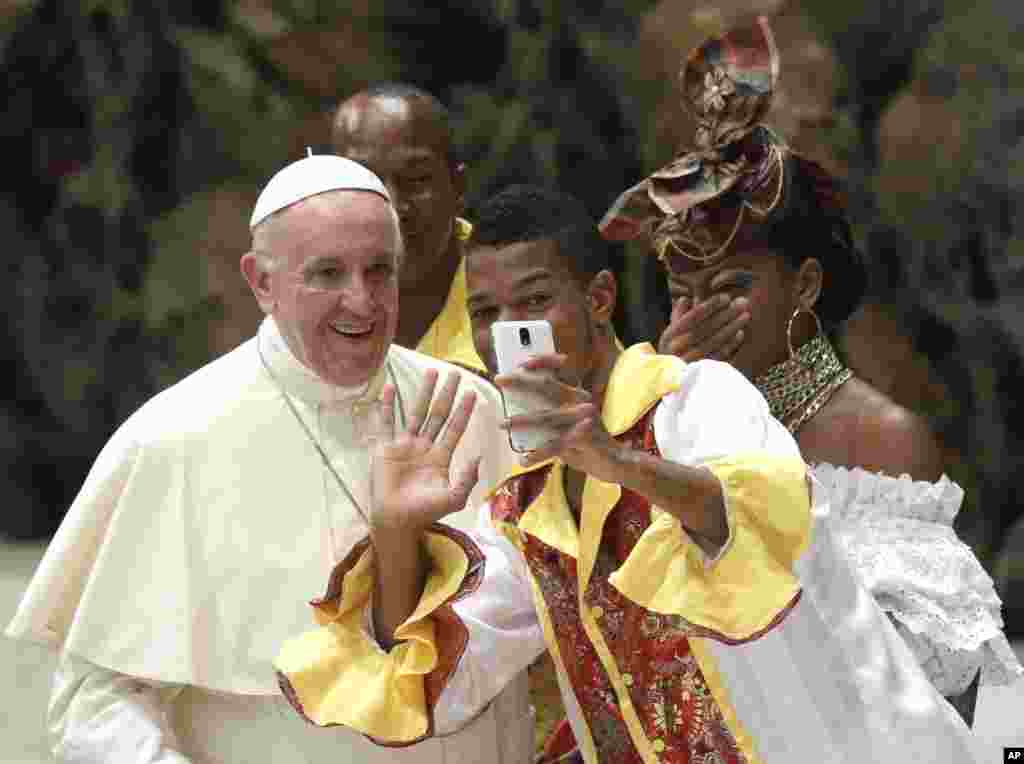 A pilgrim takes a selfie with Pope Francis before the start of the weekly general audience in the Paul VI Hall at the Vatican.