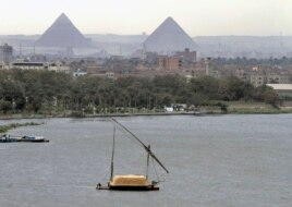 n this file photo of January 22, 2013, a traditional felucca sailing boat carries a cargo of hay as it transits the Nile river passing the Pyramids of Giza in Cairo, Egypt.