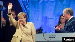 German Chancellor Angela Merkel waves next to Christian Democratic Union (CDU) leader and top candidate for chancellor Armin Laschet during his election rally in Stralsund, Germany, Sept. 21, 2021.