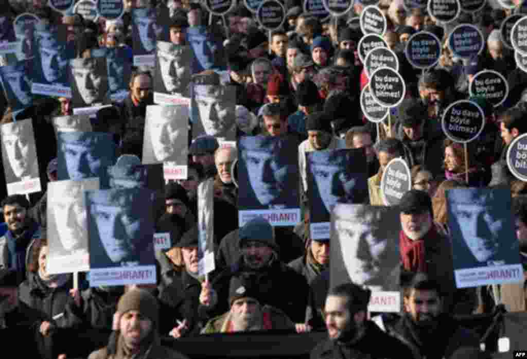 Hundreds of people hold placards that read 'This case won't end this way' and showing a portrait of Hrant Dink, outside a courthouse in Istanbul, Turkey, Tuesday, Jan. 17, 2012. A prosecutor is demanding life imprisonment for seven men accused of involve