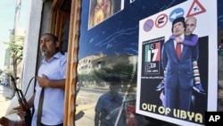 A Libyan rebel stands by a shop window decorated with a portrait of Moammar Gadhafi with his son Seif al-Islam on his shoulders, in Tripoli, Aug. 25, 2011