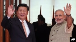 17일 인도를 방문한 시진핑 중국 국가 주석(왼쪽)이 나렌드라 모디 인도 총리와 함께 취재진을 향해 손을 흔들고 있다.