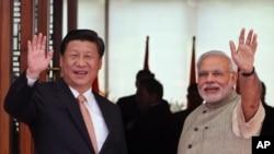 PM India Narendra Modi (kanan) dan Presiden China Xi JInping melambaikan tangan kepada media, setibanya di sebuah hotel di Ahmadabad, India, Rabu (17/9).