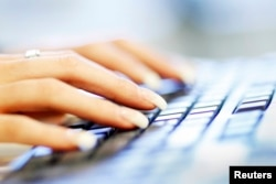 FILE - A woman uses a computer keyboard in this photo illustration taken in Sydney, Australia, June 23, 2011.