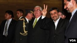"Presiden Iran Mahmoud Ahmadinejad mengacungkan tanda ""V"" (victory) saat tiba di Quito, Ekuador (13/1)."