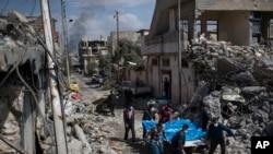 当地居民扛起在联盟空袭中丧生的人的尸体。