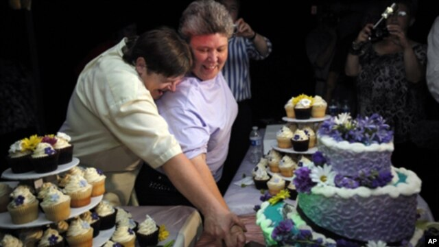 Kitty Lambert, right, and Cheryle Rudd cut their wedding cake at their reception before their wedding in Niagara Falls, N.Y.