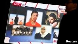 1月29日東京街道一名行人觀看電視上有關約旦飛行員卡薩斯巴與日本記者后藤健二命運的消息。