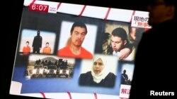 Seorang pria di Tokyo berjalan melewati layar televisi yang menayangkan berita mengenai pertukaran sandera dengan tahanan Yordania.