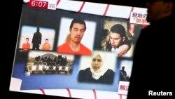 Čovek prolazi pored TV ekrana na kojem se emituje vest o taocima u rukama Islamske države