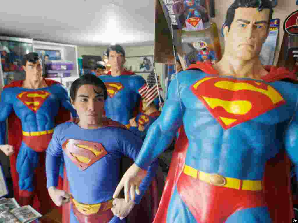 "Herbert Chavez poses with his life-sized Superman statues inside his house in Calamba Laguna, south of Manila October 12, 2011. In his idolization of the superhero, Chavez, a self-professed ""pageant trainer"" who owns two costume stores, has undergone a se"