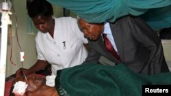Tanzania's Vice President Mohamed Gharib Bilal consoles a faithful at Mount Meru Hospital, who was injured during an explosion at the new Catholic church, in the northern Tanzanian town of Arusha, May 6, 2013.