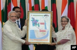 FILE - Bangladesh's Prime Minister Sheikh Hasina and Indian Prime Minister Narendra Modi hold a location map of Indian Economic Zones during an agreement program in Dhaka, Bangladesh, June 6, 2015.
