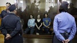 Feminist punk group Pussy Riot members, from left, Yekaterina Samutsevich, Maria Alekhina and Nadezhda Tolokonnikova sit in a glass cage at a courtroom in Moscow, Russia, Aug 17, 2012.