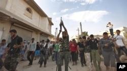 Một tay súng bắn lên không trong đám tang của 1 binh sĩ phe nổi dậy, Husain Al-Ali, bị thiệt mạng trong vụ đụng độ ở Aleppo, 9/8/2012