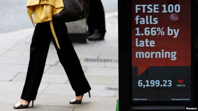A woman passes an electronic sign showing the FTSE 100 index, in the City of London, July 3, 2013.