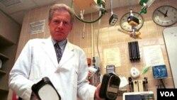 Seorang dokter menunjukkan alat kejut listrik (defribillator) jantung model lama. Makin banyak studi menunjukkan arus tegangan tinggi bisa merusak sel-sel otot jantung sendiri.