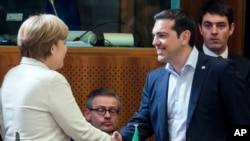 Greek Prime Minister Alexis Tsipras, right, shakes hands with German Chancellor Angela Merkel during a round table meeting at the EU-CELAC summit in Brussels on Wednesday, June 10, 2015.