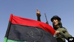 A rebel fighter gestures beside a Kingdom of Libya flag on a truck at a staging area to the east of Brega, April 4, 2011