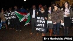 """Quelques personnes tiennent des calicots avec mention """"justice au Burundi"""" et """"la vie des Burundais d'abord"""" durant le recueillement devant la Maison Blanche, en mémoire des victimes de la tuerie du weekend dernier dans certains quartiers de Bujumbura, au"""