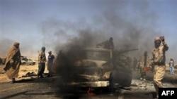 Các thành viên nhóm nổi dậy quan sát một quân xa của lực lượng thân ông Gadhafi bị hư hại vì cuộc oanh kích của NATO