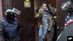 Ukrainian Security Service officers detain former Georgian president Mikheil Saakashvili at the entrance of his apartment building in Kyiv, Ukraine, Dec. 5, 2017.