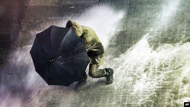 A man uses an umbrella as Turkish riot police fire water cannons and tear gas at hundreds of demonstrators who try to march to Taksim Square in Istanbul, Feb. 8, 2014.