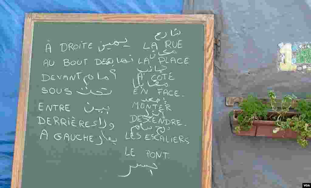 Kata-kata dalam Bahasa Arab dan Perancis di papan tulis di sekolah migran di Calais, Perancis.(VOA/L. Bryant)