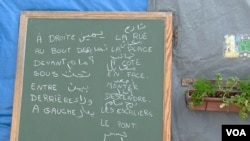 Words in Arabic and French are seen on a chalk board at a migrant school in the Jungle camp in Calais, France. (L. Bryant/VOA)