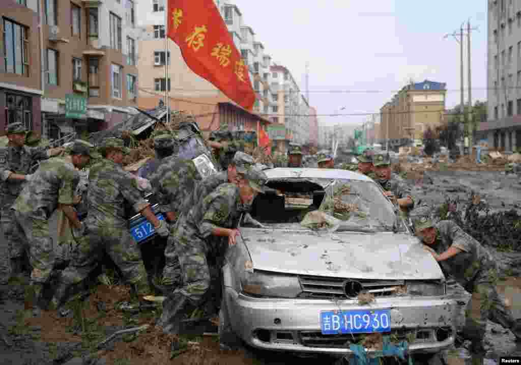 Para petugas penyelamat mendorong sebuah mobil yang rusak keluar dari genangan lumpur setelah banjir surut di Yongji, Jilin, China.