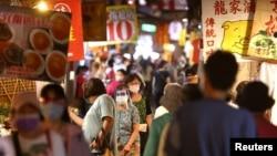 台灣台北市民眾戴著口罩逛夜市。(2021年7月6日)