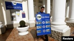 A man carries a placard with currency rates at a currency exchange office in Sevastopol, Ukraine, March 24, 2014.