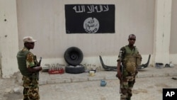 FILE - Soldiers stand at a checkpoint in front of a Boko Haram flag the Nigerian city of Damasak, Nigeria, March 18, 2015. In Senegal, 29 suspects are awaiting a ruling on terrorism-related charges. Most of the suspects are believed to have fought for Boko Haram in Nigeria, while others fought for jihadists in Libya and Mali.