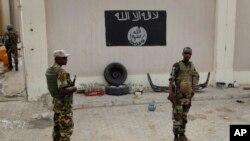 Des soldats se tiennent à un poste de contrôle devant un drapeau de Boko Haram dans la ville nigériane de Damasak (Nigéria), le 18 mars 2015.