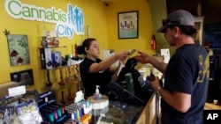 FILE - Jessica Mann, left, gives change to a customer following a recreational marijuana purchase at Cannabis City, in Seattle, July 7, 2016. Officials in states like Oregon where marijuana is legal are trying to curtail smuggling of pot to other states. Meanwhile, U.S. Attorney General Jeff Sessions is pushing for a more aggressive approach in these states, noting the drug is being diverted to other states.