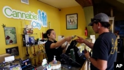 FILE - Jessica Mann, left, gives change to a customer following a recreational marijuana purchase at Cannabis City, in Seattle, July 7, 2016. Officials in states like Oregon where marijuana is legal are trying to curtail smuggling of pot to other states.